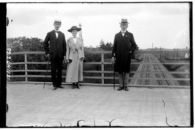 Hålahult sanatorium, exteriör, två män och en kvinna står på en bro över järnvägen, uppklädda, Ervalla stationen?