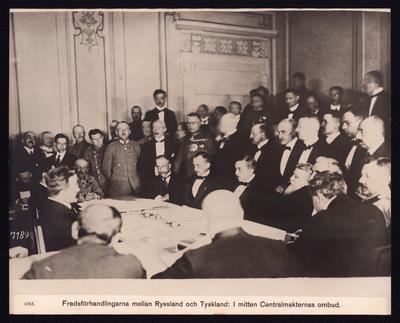 Bilden föreställer fredsförhandlingarna mellan Ryssland och Tyskland. Man ser ett fler tal finklädda herrar som sitter runt ett bord. Det omgivande rumet är fyllt med fler herrar med civil beklädnad och uniformer.