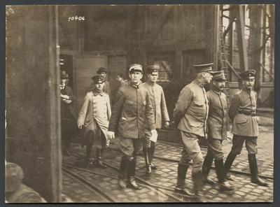 Bilden visar en grupp militärer på väg genom ett industriområde.