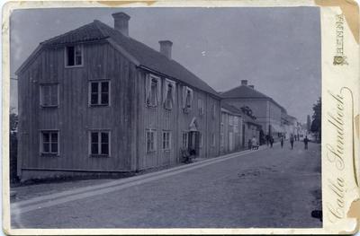 Brahegatan i Gränna med S A Andrée födelsehus närmast till vänster, en tvåvåningsbyggnad med locklistpanel och valmade gavlar. Markiser vid tre av andra våningens fem fönster. En skylt ovanför dörren: