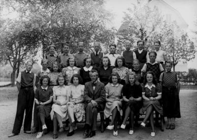 Almby skola, 12 flickor, 12 pojkar och lärare Albert Johansson på skolgården. Klass 7. Skolbyggnad i bakgrunden.