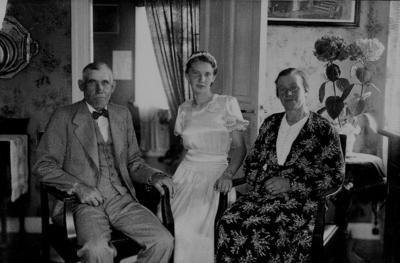 Rumsinteriör, familjegrupp 3 personer. Samuel Larssons familj. Från vänster : Samuel Larsson f.1879 d.1946, dottern Brita Larsson (gift Eriksson) f.1923 d.2000 och Anna Larsson f.1889 d.1974.