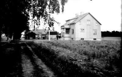 Envånings villa med inredd vind, frontespis, balkong och förstebro. Familjegrupp 3 personer framför huset. Alf. Andersson