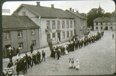 Logen Margareta i demonstrationståg på Stortorget i slutet av 1890-talet. Utanför Kappers raksalong står Kappers dotter Anina, syster till järnhandlare K.J. Wibergs fru, född Olga Kappers. Polisen är konstapel Norén. Vid x går den gamle nykterhetskämpen Hall. Alfr. Jonssons båda hus till vänster.