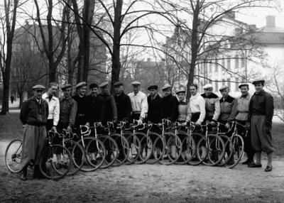 16 cyklister, Nerikes Cykelförbund.  Plats i Oskarsparken. I bakgrunden till vänster Stockholmshuset och till höger Oskarsparken 1, 3