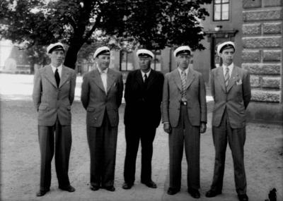 Familjegrupp 5 personer, studenter.  Waldemar Tegner med sina fyra söner. Från vänster: Per Tegner född 1912, Harald Tegner född 1905, pappa Waldemar född 1875 i Liverpool, Gunnar Tegner född 1910, Botvid Tegner född 1914. Stadsfogde Waldemar Tegner, Ekersgatan 8, Örebro. Bilden är tagen på Karolinska skolans skolgård.