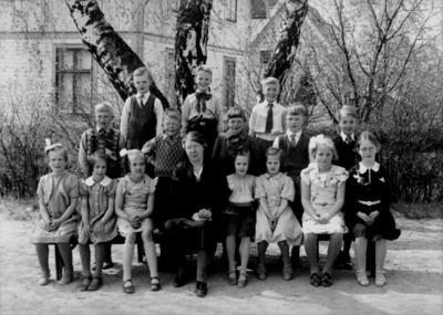 Rynninge skola, 7 flickor, 8 pojkar och lärarinna fru Elsa Andersson på skolgården. Skolbyggnad i bakgrunden.