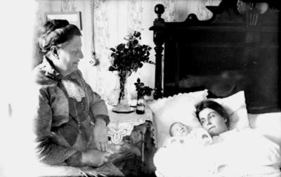 Rumsinteriör. Yngre kvinna liggande i säng med ett spädbarn bredvid sig. Äldre kvinna sittande bredvid sängen Kan vara en nyförlöst kvinna med sitt nyfödda barn Hulda Lindskog