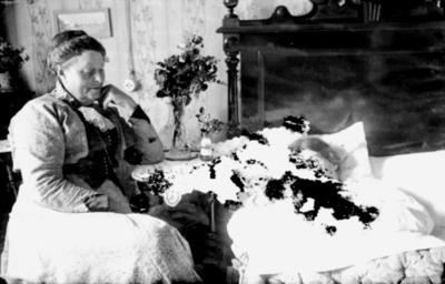 Rumsinteriör. Liggande kvinna med baby, sittande kvinna. Kan vara en nyförlöst kvinna med sitt nyfödda barn Hulda Lindskog