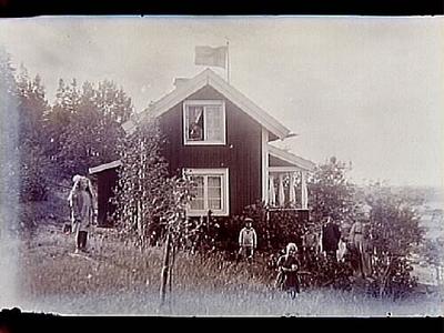 Sommarstugan Fridensborg, envånings sommarstuga med inredd vind och veranda åt vänster. Fem barn och två vuxna vid stugans gavel. Fotograf Sam Lindskog