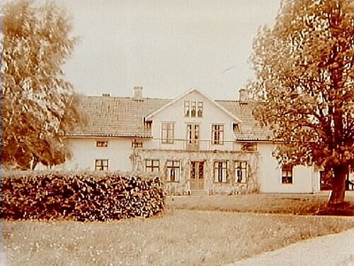 En och en halvvånings bostadshus med frontespis, veranda som är glasad och balkong. Johan Persson