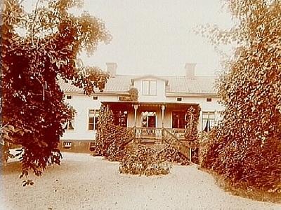 En och en halvvånings bostadshus med takhuv och veranda i snickarglädje. Handlare Bergs gård på söder där nu Södra Allén går fram. (Firma Berg & Gylander)
