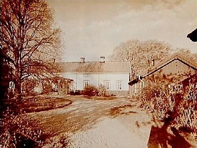 En och en halvvånings bostadshus med veranda i snickarglädje. Till höger på bilden envånings bostadshus. Kyrkoherde Ivar Jäderlund. Beställningsnr: GR-135.
