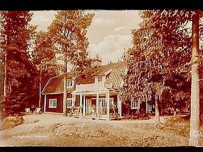 Sommarvilla vid Norra Lången, envånings sommarvilla med inredd vind, brutet tak, två fönsterhuvar, stor veranda med balkong.  Bilden tagen till vykort. Överstelöjtnant Gustaf Malmros
