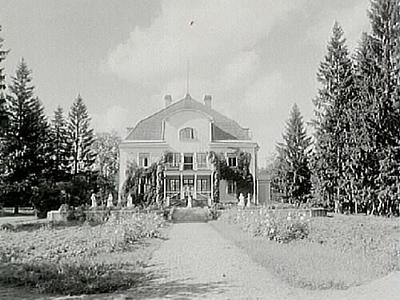 Tvåvånings bostadshus med brutet tak och frontespis, veranda och balkong. Nio barnsköterskor framför huset. Syster Torborg Törnkvist. Holmsätershemmet.