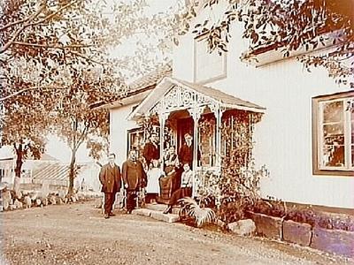 En och en halvplans bostadshus med frontespis, veranda med snickarglädje. Växthus. 7 personer på trappan till verandan. Direktör Erik Zetterlöf Eriksdal, Örebro.