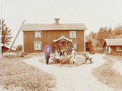 Tvåvånings bostadshus med veranda i snickarglädje. Lågt uthus. Fyra vuxna och tre barn varav en på gunghäst. Elof Bolinder