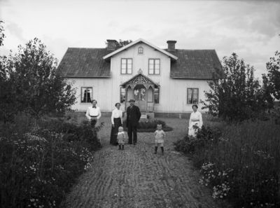 Envånings bostadshus med inredd vind, frontespis och veranda med snickarglädje. 6 personer framför byggnaden. Gustaf Eriksson