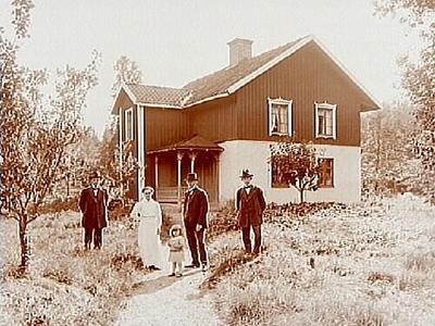 Tvåvånings bostadshus med veranda och trapphus. 3 män, en kvinna och ett barn framför huset. Ernst Pettersson.