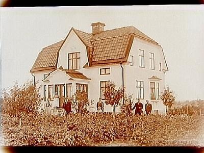 En och en halvvånings villa med frontespis, burspråk, glasad veranda och brutet tak. 10 personer framför villan. P.G. Broström