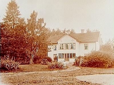 Tvåvånings bostadshus med glasad veranda och balkong. Tre personer framför huset. Erik Andersson
