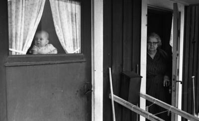 Gyttorp 2 23 februari 1967  Från en bostad står en kvinna i dörröppningen. På bilden ser man också ett litet barn i fönstret på dörren titta ut.