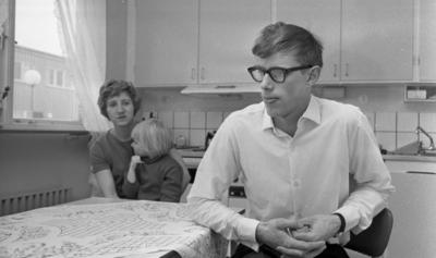 Gyttorp 23 februari 1967  En kvinna sitter med ett barn i famnen vid ett bord i köket. En man med glasögon och vit skjorta sitter också vid bordet.