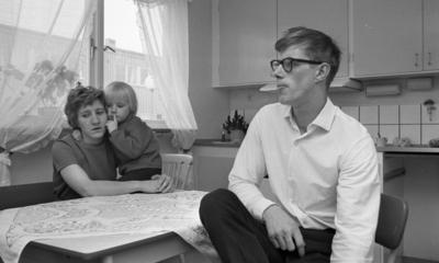 Gyttorp 23 februari 1967  En kvinna sitter med ett barn i famnen vid ett bord i köket. Det sittter också en man med glasögon och vit skjorta vid bordet.