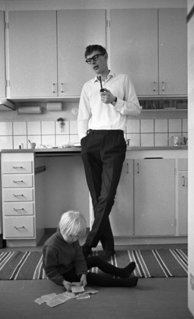 Gyttorp 23 februari 1967  En man med glasögon och vit skjorta står vid diskbänken och röker pipa. Framför honom sitter en flicka på mattan och leker med en kortlek.