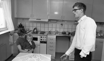 Gyttorp 23 februari 1967  Vid bordet sitter en kvinna med en flicka i famnen. En man med glasögon och vit skjorta står vid en stol.