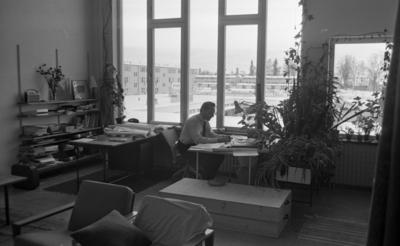 Konstig konst 16 december 1966  En arkitekt sitter och ritar vid ett bord inne på ett kontor. Han är klädd i en vit skjorta, svart slips och svarta byxor. På en hylla i bakgrunden står två tavlor lutade mot väggen.
