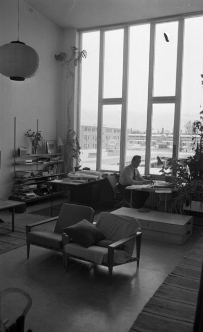 Konstig konst 16 december 1966  En arkitekt sitter och ritar vid ett bord inne på ett kontor. Han är klädd i en vit skjorta, svart slips och svarta byxor. I förgrunden står två fåtöljer.