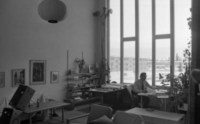 Konstig konst 16 december 1966  En arkitekt sitter vid ett bord på ett kontor och bläddrar med papper. Två fåtöljer syns i förgrunden. En hylla syns i bakgrunden till vänster.