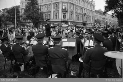 Marknadsafton 13 juni 1969  Framför Nikolai kyrkan spelar en orkester med blåsinstrument. På gatan ser man mycket folk som går, och står och tittar.