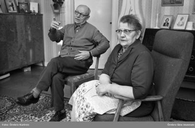 Rynninge 19 februari 1969  En kvinna i klänning och glasögon sitter i en fåtölj, och en man med glasögon sitter på en stol i ett rum. På ett skåp och en byrå står det fotografier.