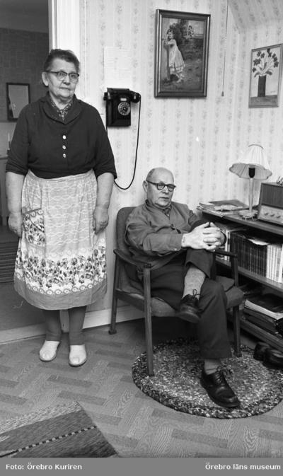 Rynninge 19 februari 1969  En kvinna i klänning och förkläde står i ett rum. På väggen hänger det en telefon. Nedanför telefonen sitter det en man med glasögon på en stol.