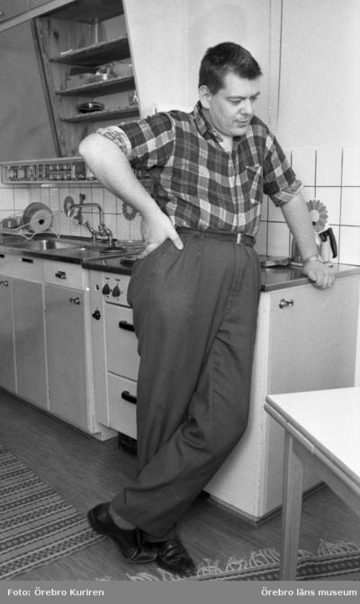 Dagmamma, manlig 11 juni 1970  Det står en manlig dagmamma i rutig skjorta vid spisen i köket. Det ligger randiga mattor på golvet.