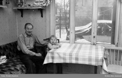 Gamla söder 27 januari 1970  En man i rutig skjorta sitter på en soffa i köket. På en stol vid bordet med rutig vaxduk sitter en pojke.