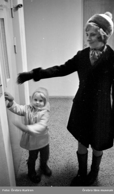 En kvinnas dagbok, Hemmafru Göhle 7 december 1970  Det står en kvinna i kappa och mössa med sitt barn och väntar på hissen.