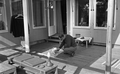 Hasselfors bruk 19 augusti 1965  En liten flickbaby som på huvudet har en liten hätta samt är klädd i liten blus och underbyxor ligger på en veranda vid ett hus vid Hasselfors bruk. Hon ligger på mage. Bredvid henne sitter en äldre man på huk och klappar henne på vänster axel med sin högra hand. Till vänster invid vägen står en dockvagn. Över denna hänger en ställning med två herrkavajer på galgar. I förgrunden står två bänkar. På den ena ligger leksaker samt två stolsdynor. I bakgrunden syns ett litet bord med duk på. Vi sidan om bordet står en liten barnstol. Ovanpå duken står en leksaksbil. Under det lilla bordet ligger en boll. Till vänster i bakgrunden är en öppen dörr som leder in till ett hus med en liten trätrappa framför. Ovanför dörren hänger en ampel med en blomma i. Inne i huset vid fönstret står en kvinna iklädd förkläde och tittar ut genom fönstret.