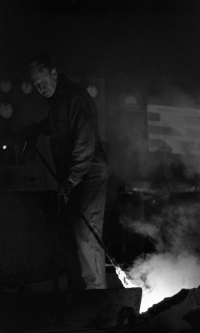 Johnson metall, 21 januari 1966  På bilden syns en metallarbetare iklädd arbetsoverall, keps och livrem i sitt arbete med metall vid ugnen på