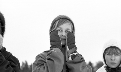 Hästnäs, 20 januari 1966  På bilden syns två flickors ansikten. Centralt i bildens förgrund syns det en flicka som är klädd i vinterkläder. Flickan har vantar på sina händer som hon håller vid sina kinder, handflatorna är vända in mot kinderna. Den andra flickan som syns åt höger i förgrunden har en ljus stickad vintermössa på sitt huvud.