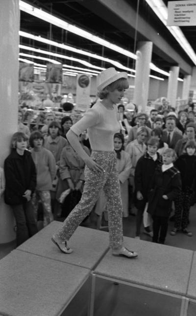 Baddräkter 12 maj 1966  En fotomodell i vit blus, färgglada byxor med bubbelmönster på, vit hatt samt sandaler går på catwalken. Publik står nedanför och tittar på.                                                                                                                 or. Han går nedför en kort trappa utomhus.