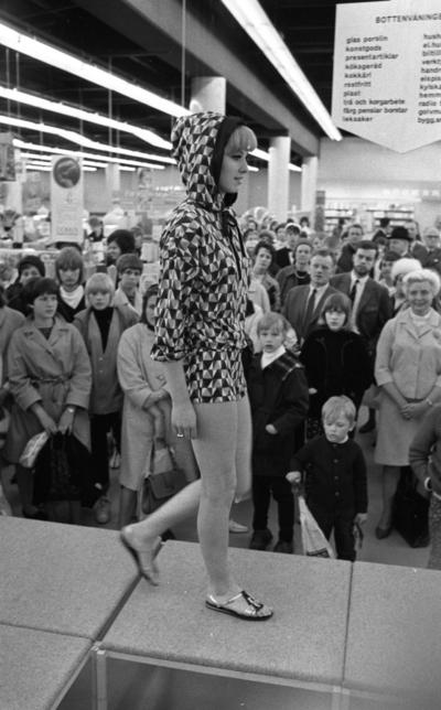 Baddräkter 12 maj 1966  En fotomodell iklädd rutig munkjacka och shorts samt med sandaler på fötterna går på catwalken. Nedanför i bakgrunden syns publik.                                                                                                                 or. Han går nedför en kort trappa utomhus.