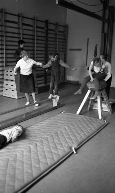 Särskolan 9 april 1966  Ett antal barn, pojkar och flickor, gör gymnastikövningar som kullerbyttor på en lång madrass i en gymnastiksal tillsammans med en lärarinna. I salen finns redskap som plint, bänk och häst