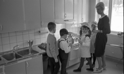 Barndaghem 29 mars 1966  På bilden syns det två flickor, två pojkar och en kvinnlig lärare stående vid spisen. Båda flickorna bär bagarmössa, förkläde, strumpbyxor och skor på sig. På en av flickorna syns det hårtoffsar. En av pojkar bär ljus skjorta, pullover, fluga och mörkare byxor. En anna pojke är klädd i en ljusare skjorta med flyga och mörkare byxor med hänge. Lärarinna bredvid barnen är klädd i en mörk klänning med en ljusare krage och ljusare skor.      På spisen syns det några kaffepannor. Ovanför spisen finns det en spisfläkt. Bullar på plåten, en mått av metall syns det på diskbänken till vänster av spisen. Ovanför diskhon syns det en köksskåp, en hållare för hushålls papperrulle, olika förvaringsfack för, exempelvis, mjöl och socker. Strykbrädan står intill fönstret till höger. Telefonapparat står på fönsterbreddan. Persienner syns i fönsterrutor.