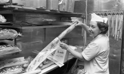 Henning Kjellgrens bageri,18 april 1966  En kvinna i vita arbetskläder samt vit hatt på huvudet håller i en påse med vänstra handen. På påsen står texten