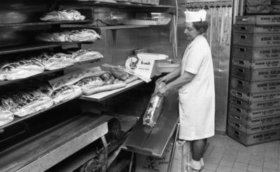 Henning Kjellgrens bageri,18 april 1966  En kvinna i vita arbetskläder samt vit hatt på huvudet håller i en påse med vänstra handen. I högra handen håller hon i ett ljust, avlångt bröd som håller på att lägga i påsen. En kartong med texten