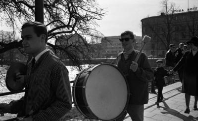Våren 29 april 1966  Närbild på några medlemmar ur en mässingsorkester: en ung man som spelar trumma samt en ung man som går framför honom (instrumentet som denne spelar på har ej kommit med på bilden). Bakom honom går en som spelar cymbal. De befinner sig på Drottninggatan. Endast instrumentet har kommit med på bild. Orkestermedlemmarna är klädda i vita skjortor och kritstrecksrandiga skjortjackor. En bit av Örebro stad syns i bakgrunden samt en kvinna med en pojke vid handen. Tre unga män sitter på broräcket i bakgrunden bakom dem. Stora Hotellet i Örebro syns också.