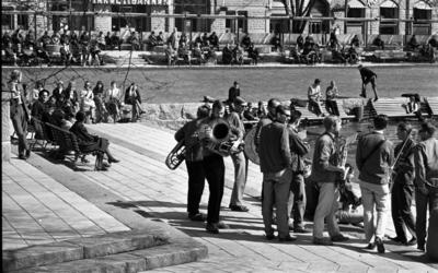 Våren 29 april 1966  En mässingsorkester står uppställd för att spela i en park i centrala Örebro. I bakgrunden syns en grupp unga flickor sitta på en stenmur och betrakta dem. Nära dem sitter personer på parkbänkar. I bakgrunden sitter också grupper av människor på parkbänkar och betraktar det hela.